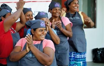 Voluntarias de un comedor comunitario de Sedesol sonriendo y aplaudiendo