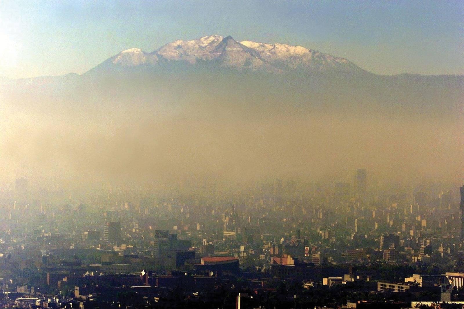 Panorámica de Ciudad de México. De fondo se ve el volcán  Iztaccíhuat y en primer plano las edificaciones de la ciudad. Cabe destacar la presencia de un gruesa capa de nubosidad contaminante entre el volcán y las edificaciones.