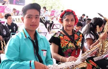Dos jóvenes originarios de pueblos indígenas con instrumentos musicales