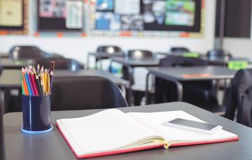 Lapicero, libreta y celular sobre pupitre en un salón de clase