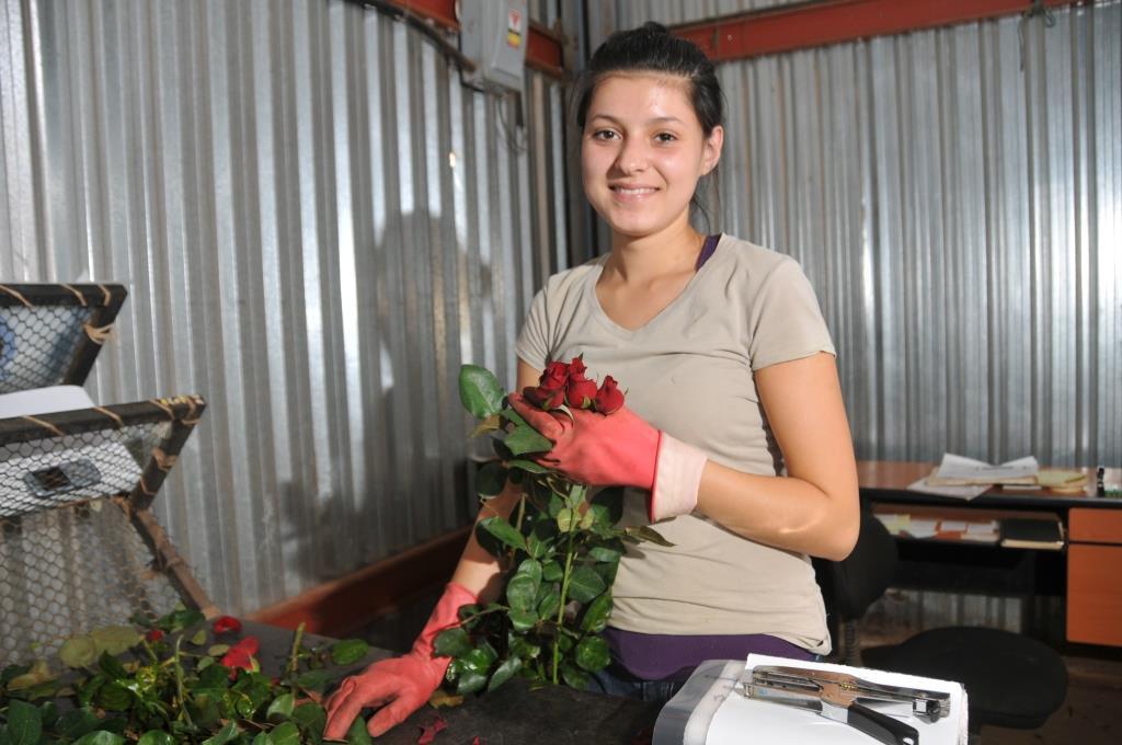 Joven mujer tiene cuatro rosas en su mano mientras sonríe a la cámara