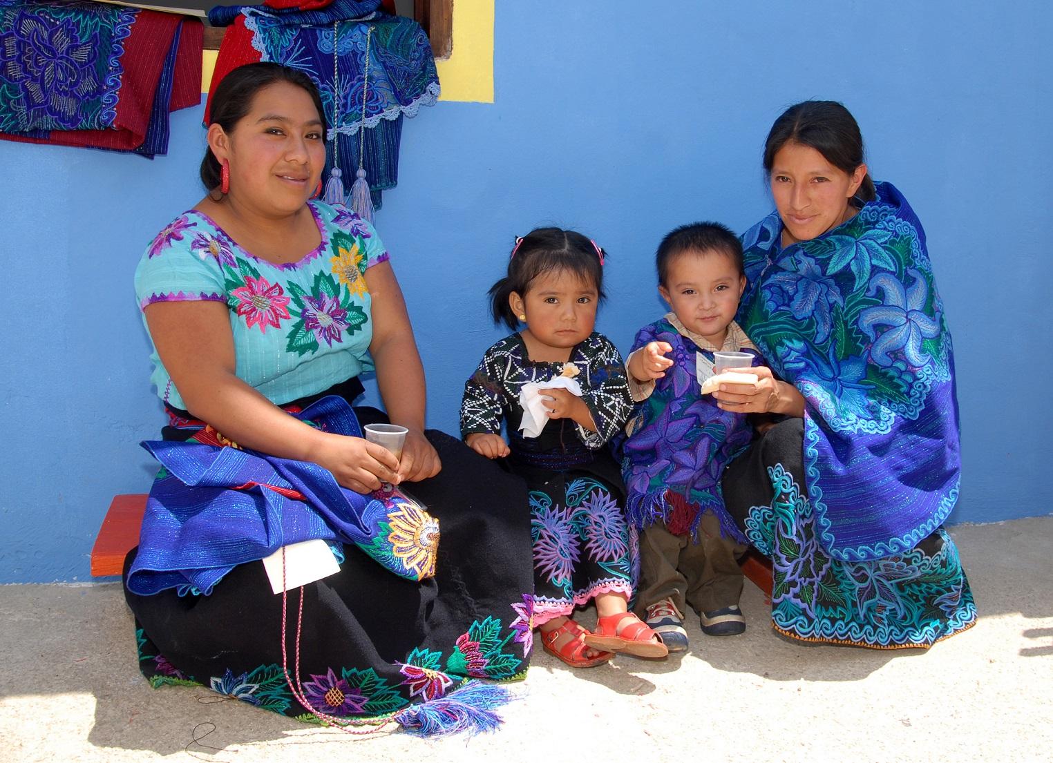 Dos mujeres con dos niños pequeños, todos con traje tradicional mexicano