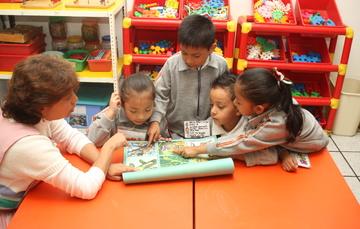 Niños viendo sus libros  de texto por primera vez.