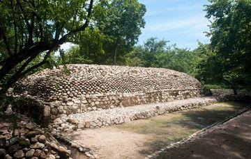 Esa imagen del Parque Eco-Arqueológico Copalita, nos muestra un basamento piramidal de la época prehispánica construido con piedras pulidas esféricas, todo  rodeado por la vegetación de la zona.