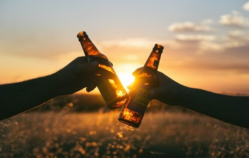 foto en contra luz de brindis con cerveza en el campo.