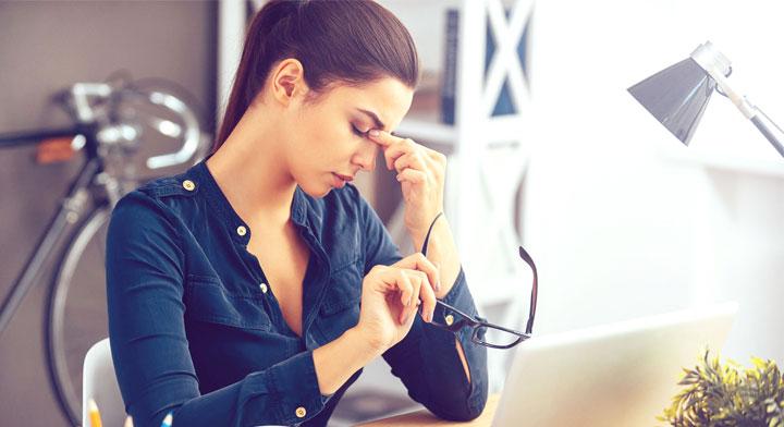 Una mujer tocándose en entrecejo y se ve muy cansada.