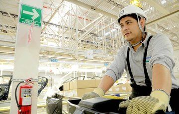 Trabajador de planta de ensamblado utilizando casco y guantes para prevenir enfermedades