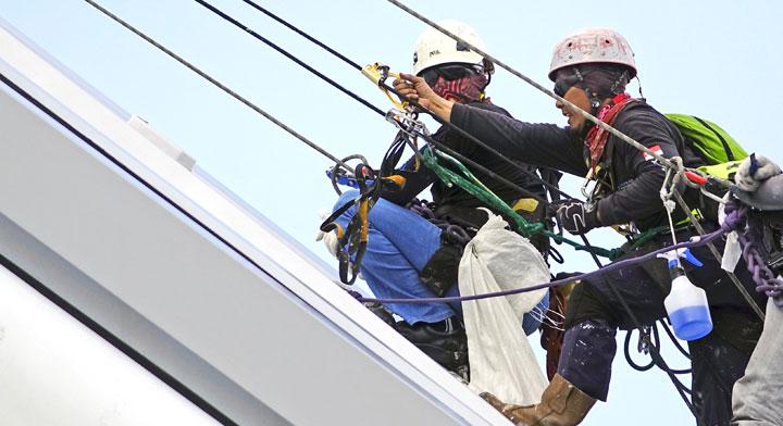 Dos trabajadores limpiando las ventanas de un edificio alto