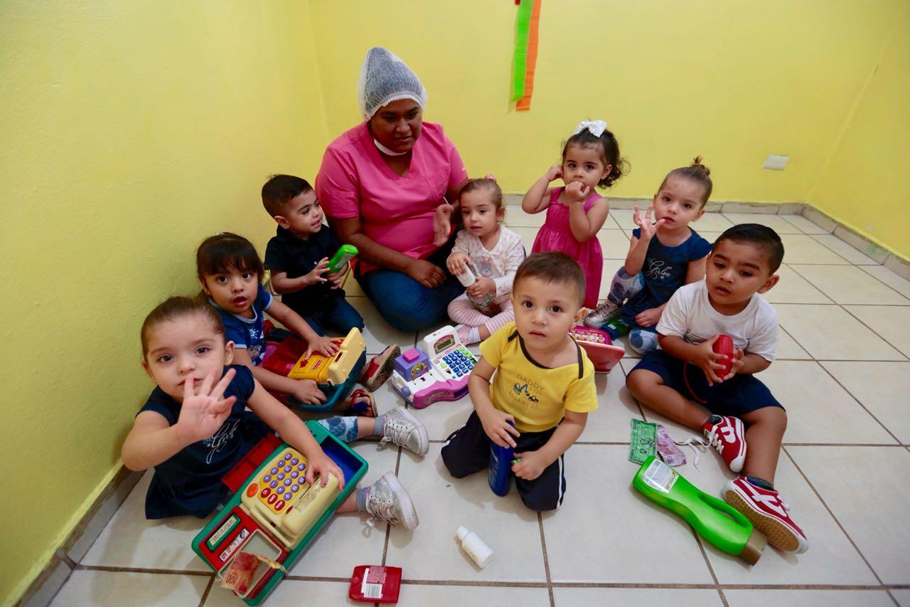 Niñas y niños sentados en el suelo acompañados de una educadora