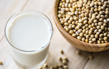 vaso de leche y taza con granos de soya