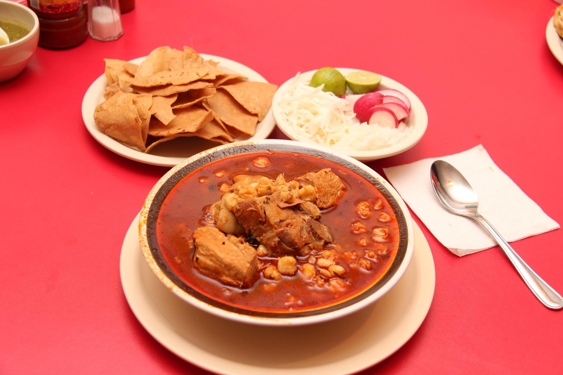 Plato de pozole rojo acompañado de tortillas fritas y condimentos