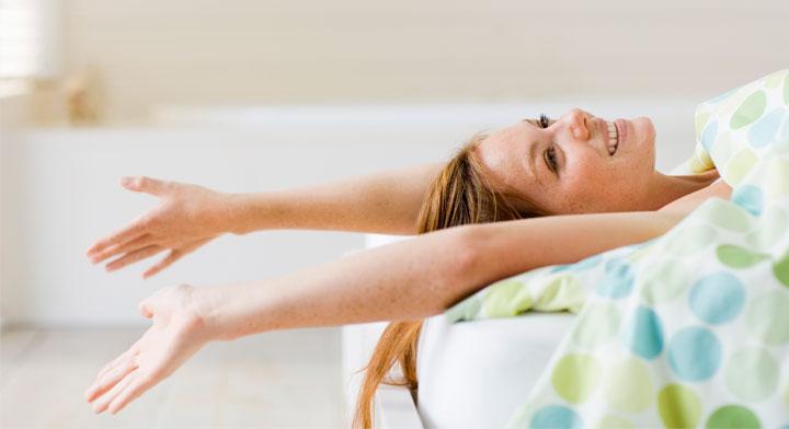 Mujer acostada en una cama y estirando los brazos y con una sonrisa en el rostro