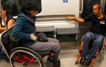 Dos personas usuarias de silla de ruedas, viajan en el metro