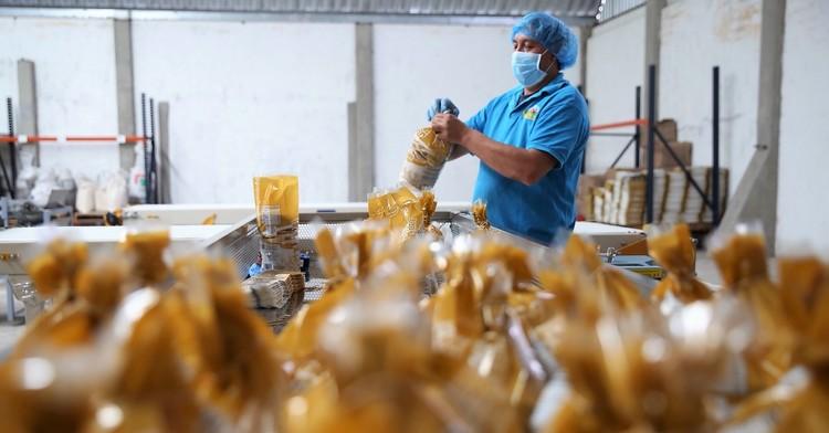 Trabajador cerrando paquete de tostadas en una empresa social