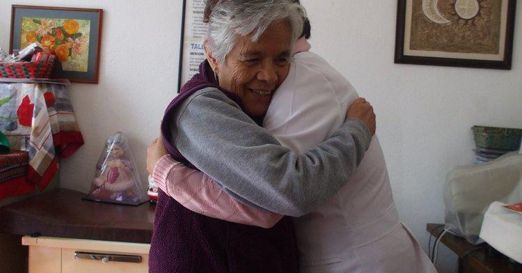 Una adulta mayor abrazando a su cuidadora