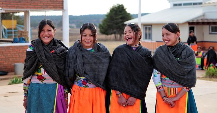 Cuatro niñas con vestimenta tradicional sonriendo