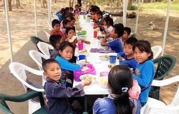 Niñas y niños comiendo en un comedor comunitario