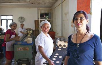 Mujeres sonriendo a la cámara mientas producen masa para galletas