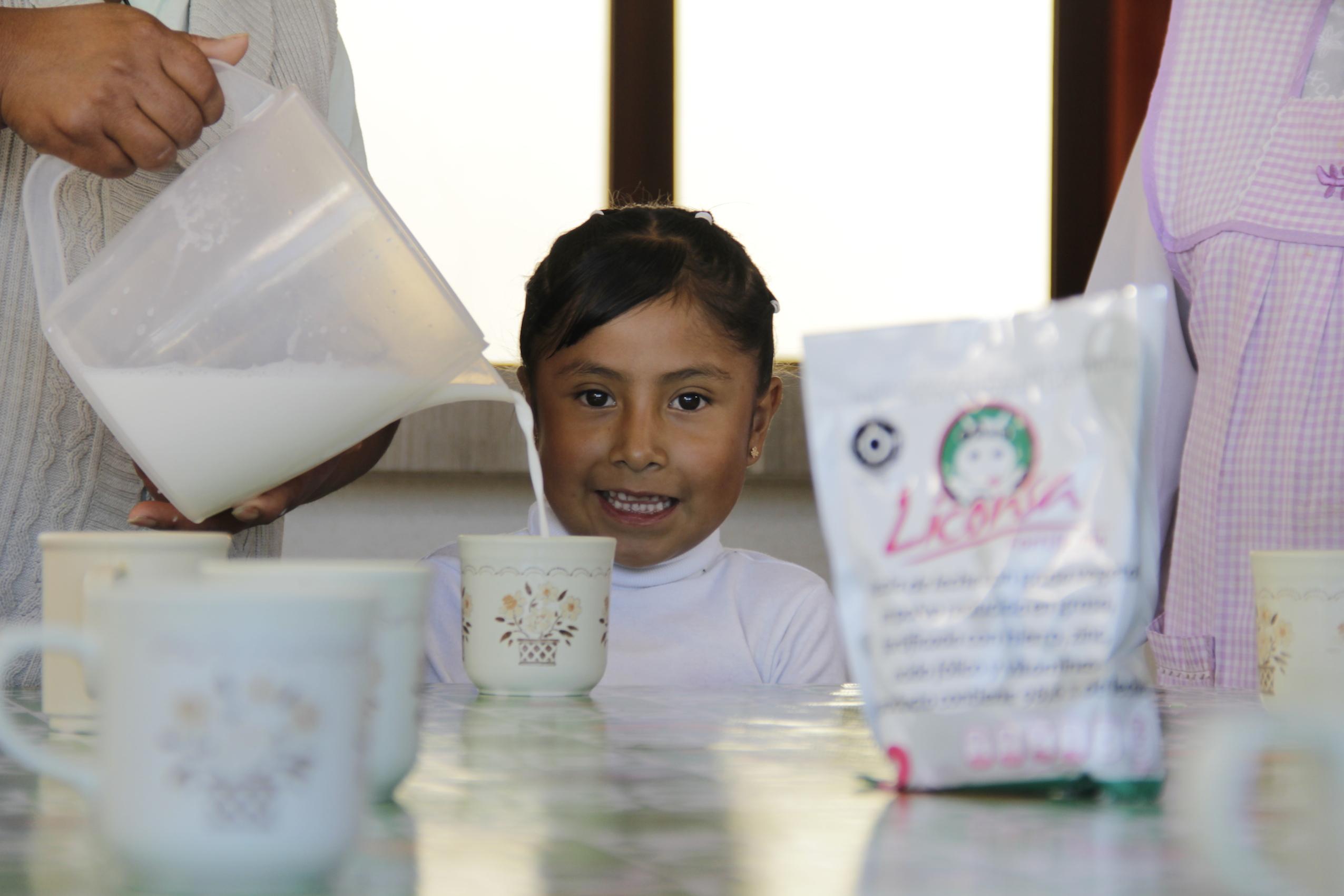 Niña sonriendo mientras alguien le sirve una taza con leche Liconsa