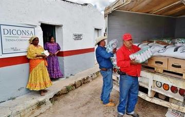 Dos personas descargando maíz Diconsa de un camión a una tienda Diconsa