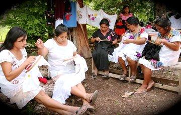 Mujeres con vestido tradicional bordando