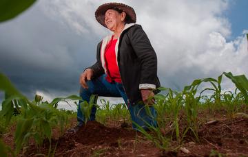 Mujer rural arrodillada en la tierra