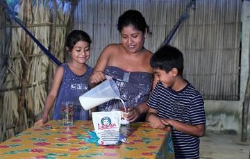 Mamá sirviendo leche Liconsa a un niño y a una niña