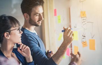 Imagen que muestra a dos personas elaborando un plan estratégico en un pizarrón blanco