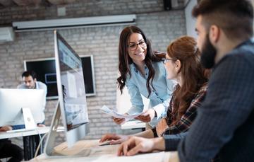 Emprendedores discuten proyecto frente a una computadora