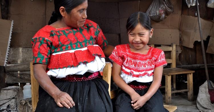 Madre e hija con vestimenta tradicional mexicana sonriendo