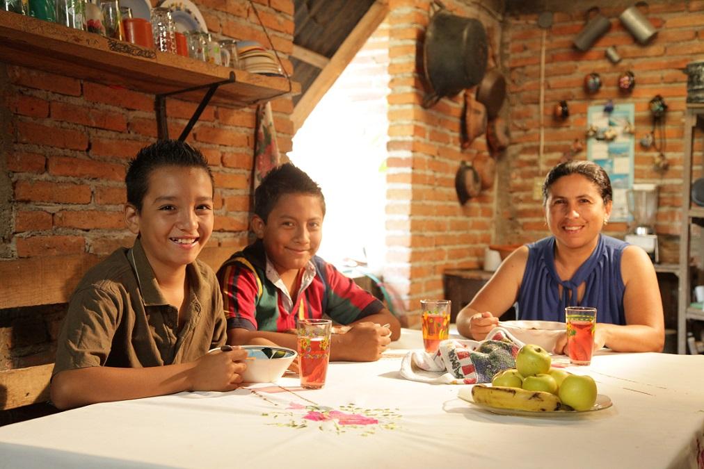 Mamá y dos hijos en el comedor de su casa sonriendo