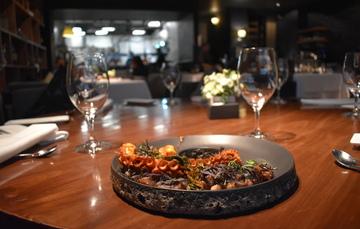 Mesa en restaurante con copas y plato servido con pulpo maya