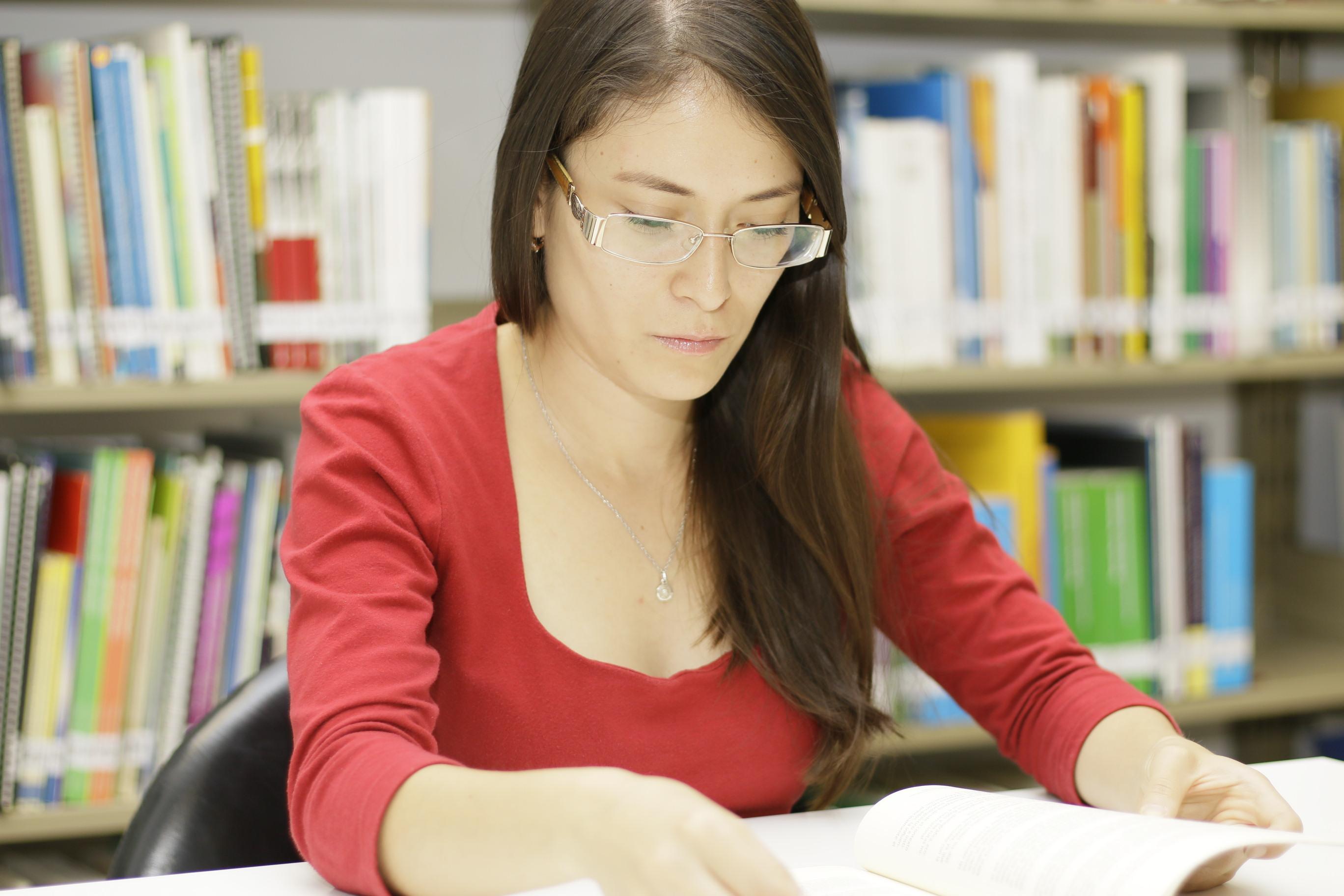 Mujer joven leyendo en una biblioteca