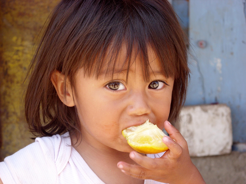 Niña pequeña comiendo una naranja