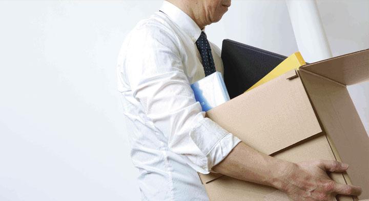 Hombre cargando una laptop, hojas y folders