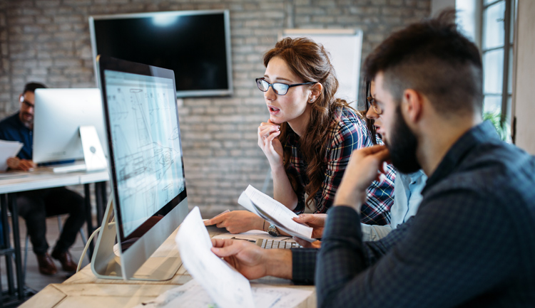Arquitectos y diseñadores trabajan frente al ordenador en un proyecto