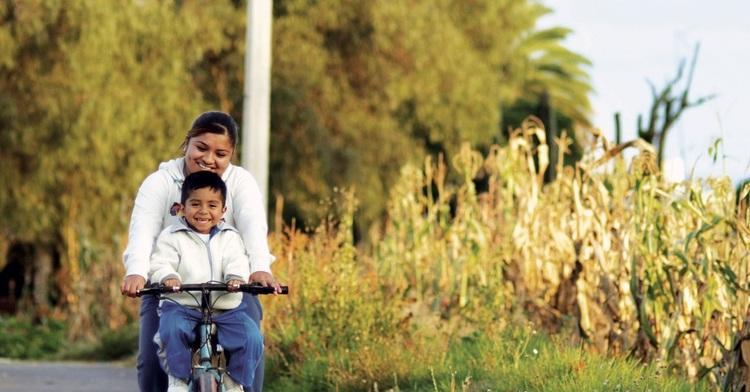 Mamá con su hijo, ambos paseando en bicicleta