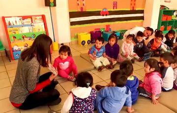 Salón de Guardería del IMSS donde niñas y niños menores a 5 años de edad escuchan atentos la lectura de un cuento.
