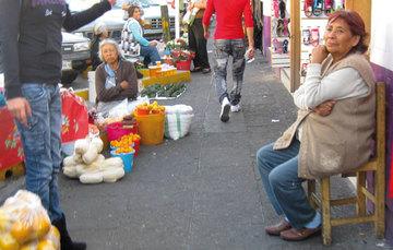 Mujeres adultas vendiendo en la calle frutas, aguadates, miel
