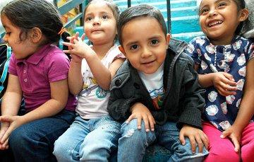 3 niñas y un niño menores de 4 años sentados en unas escaleras