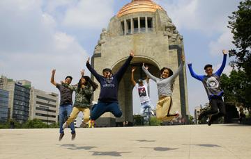 Jóvenes brincando frente al monumento a la Revolución