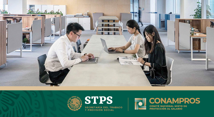 Dos mujeres y un hombres, trabajando en sus laptops, están sentados en una mesa en el centro de una bodega