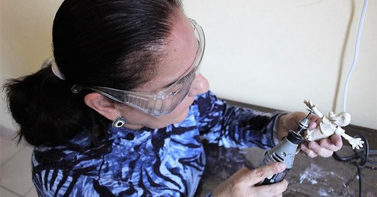 Mujer adulta mayor trabajando un modelo de plastilina