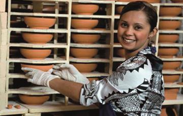 Mujer acomodando platos de barro en stock