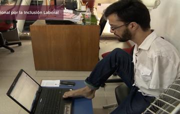 Joven sin brazos trabaja manejando la computadora con los pies en una oficina.