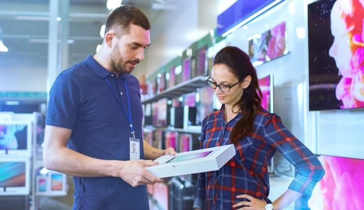 Vendedor explicando a mujer sobre las ventajas de una tableta en una tienda de equipo de tecnología