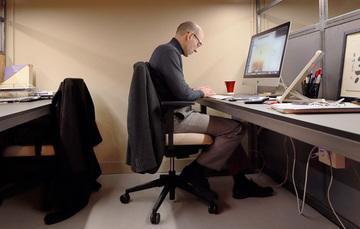 Un hombre maduro que esta sentado, trabajando en una oficina, frente a una computadora.