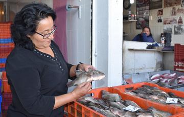 Señora comprando pescado en el Mercado de la Nueva Viga.