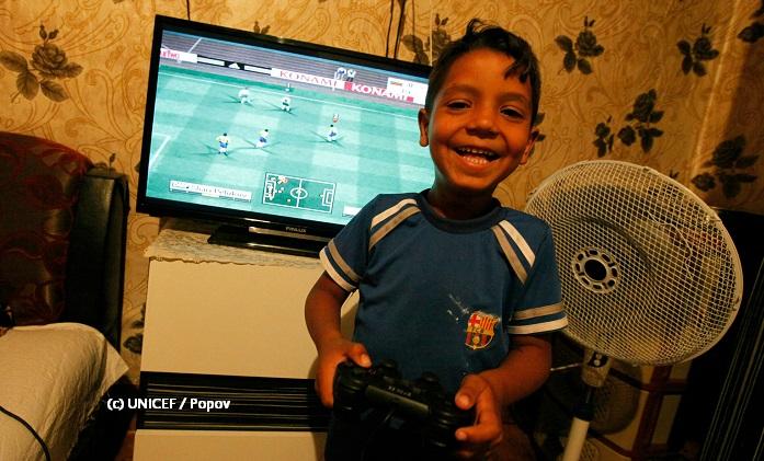 Niño con control de videojuego y en pantalla se despliega juego de futbol soccer.