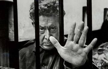 """Cartel de invitación a inauguración de la Exposición Permanente """"Siqueiros. Encarcelar la llamarada"""", en la que se incluye fotografía con Siqueiros visto a través de una reja en la prisión de Lecumberri con su brazo extendido mostrando la palma abierta"""